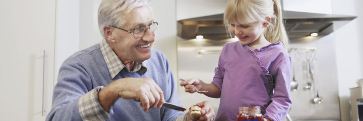 Senior man spreading jelly on cookies with young girl