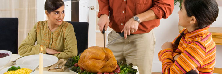 Woman and girl watch man carve turkey at table